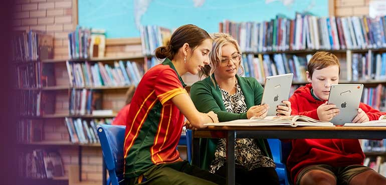 Teacher sitting in library with two students pointing to an iPad device.